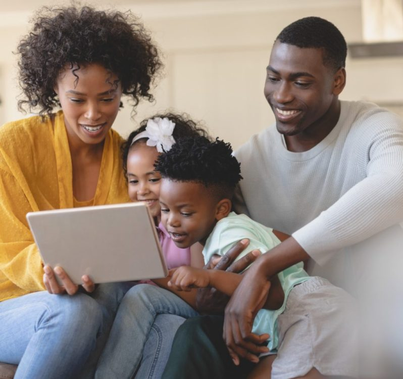Front view of happy African American parents with their cute children using digital tablet on sofa in a comfortable home